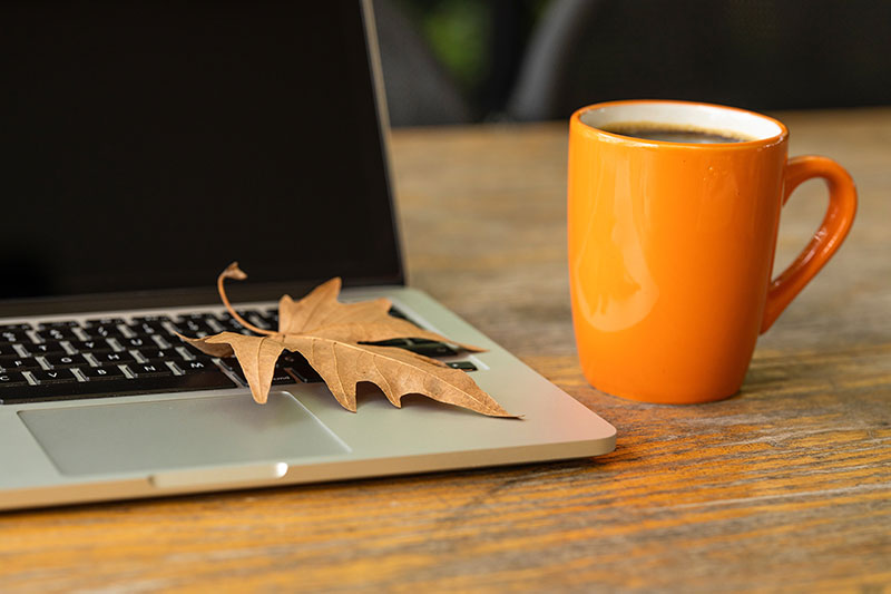 computer open with coffee cup and fall leaf